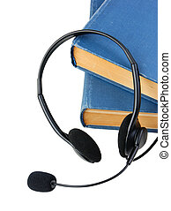 Headphones with a microphone and a stack of books isolated on white background