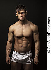 Muscular young man over black - Portrait of muscular young...