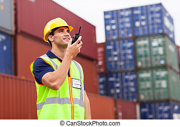 harbor worker talking on the walkie-talkie - young harbor...