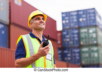 middle aged warehouse worker holding radio - smiling middle...