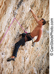 Rock climber on face of a cliff - Rock climber on a face of...