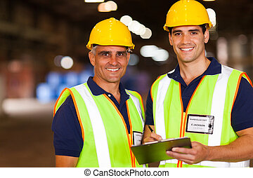 warehouse workers - two warehouse workers working inside...