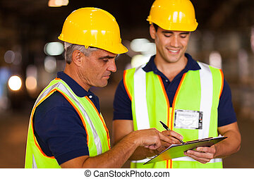 warehouse workers checking stock - two warehouse workers...