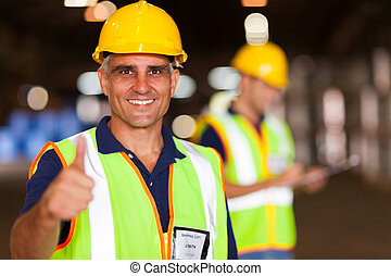 senior shipping company worker giving thumb up inside...