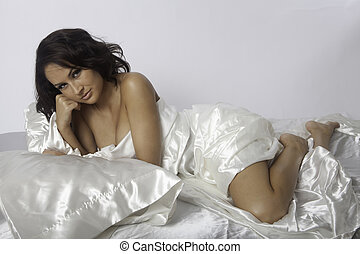 woman with white satin sheets - beautiful woman on white...