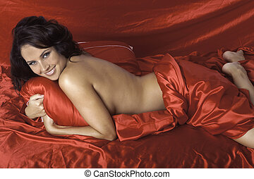 woman on red satin sheets - beautiful woman on red satin...