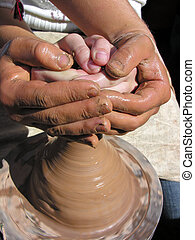 close-up of potter and child hands making pottery