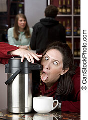 Woman drinking coffee directly from a dispenser - Woman...