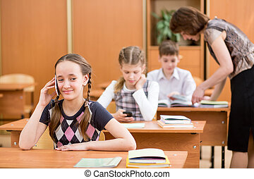 Primary school pupil using cell phone at lesson