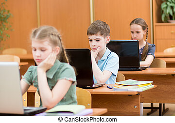 schoolkids using laptop at lesson