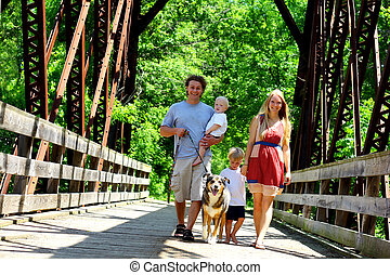 Family Walking Across Bridge - A young, attractive family of...