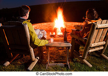 Bonfire - A couple is sitting by the bonfire, enjoying wine