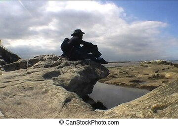 World Explorer - A man sits on a rock and contemplates...
