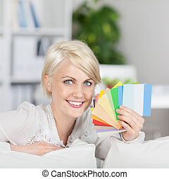 happy woman showing samples of wall color