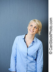 Smiling Blond Woman Against Blue Background - Portrait of a...