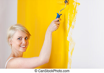 Smiling Woman Painting The Wall - Side view of a smiling...