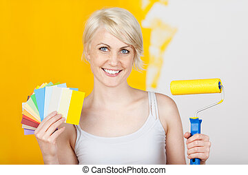 Happy Woman Holding Out Color Samples And Paint Roller -...