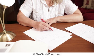 Middle-aged woman writing at the table