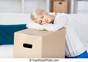 Woman Resting Head On Cardboard Box At Home