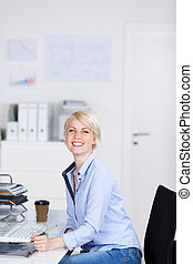 Happy Businesswoman Sitting At Office - Side view portrait...