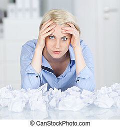 Tired executive With Crumpled Paper Balls At Desk - Portrait...