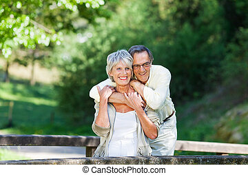 Senior Man Embracing Wife From Behind While Looking Away -...