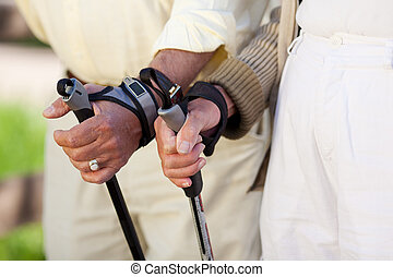 Senior Couple's Hands Holding Hiking Poles - Closeup of...