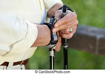 Senior Man Adjusting Hiking Pole's Strap On Hand -...
