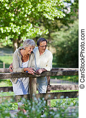 Old couple standing on a bridge inside a park - Happy old...