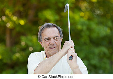 Elderly man with golf stick in action