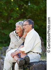Couple Looking Away While Embracing In Park - Happy romantic...