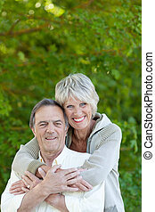 Happy senior couple - Senior woman embracing her husband at...