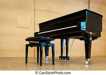 black grand piano with music stool at wooden stage