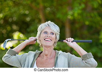 Senior Woman Holding Golf Club While Looking Away - Happy...