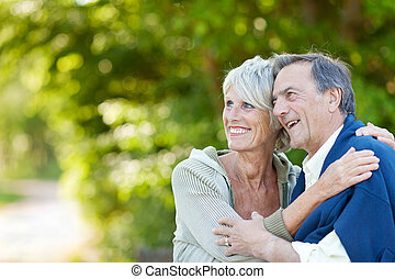 Cute elderly couple laughing - Cute elderly couple holding...