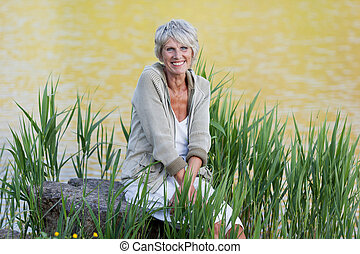 Cheerful old lady sitting near the lake - Happy and cheerful...