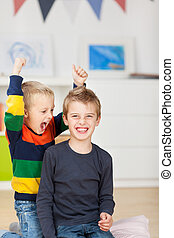 Young Boy With Wild Brother Raising Arms - Portrait of happy...