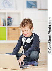 Browsing young boy with headphones - Smiling little boy...