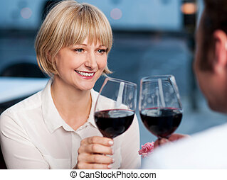Couple toasting in a restaurant - Gorgeous middle aged woman...