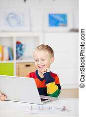 Boy Using Laptop At Table In House - Happy little boy using...