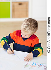 Boy Drawing On Paper At Table