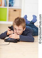 niño, piso, juego, mientras,  vídeo, juego, acostado
