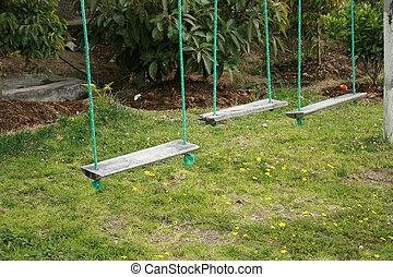 Swing Set - A handmade swing set in a field of grass in...