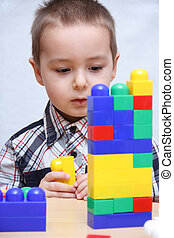 Child builds a tower with plastic blocks