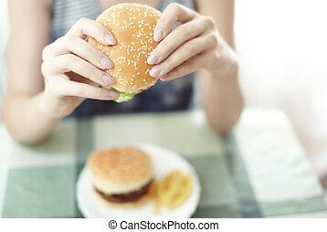 Hamburger - Woman holding hamburger and sitting at the table