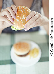 Hamburgers - Woman holding hamburger and sitting at the...