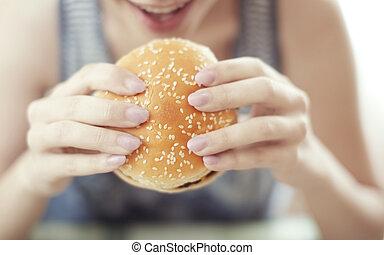 Hamburger - Woman holding and eating hamburger