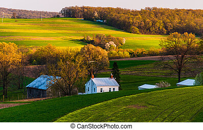 Home and barn on the farm fields and rolling hills of...