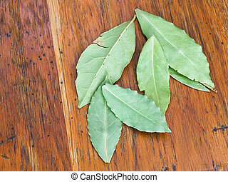 bay leaves on table - aromatic bay leaves on wooden table