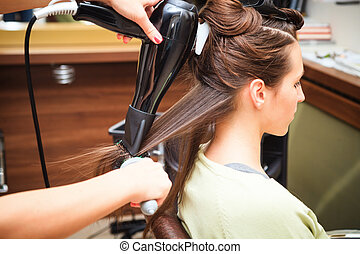 hairstyling - young woman at hairdresser do hairstyling